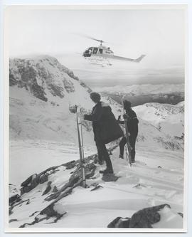 Skiers Standing on a Ridge Watching a Helicopter
