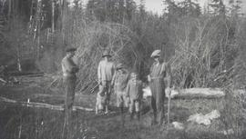 Jardine / Neiland family in front of piles of brush