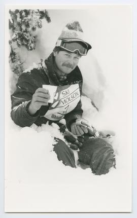 Competitive Skier Enjoying a Meal in a Snowbank