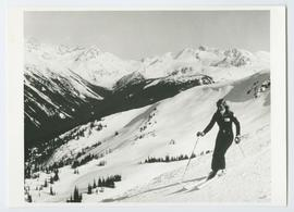 Woman Skiing with Bowls and Mountain Peaks in Background