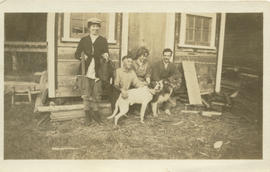 Sewall Tapley and others sitting on the steps of a cabin